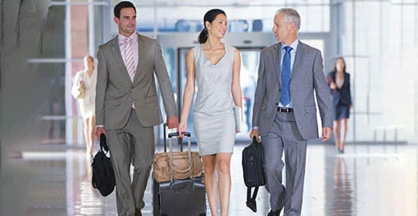 3 business travelers with suitcases