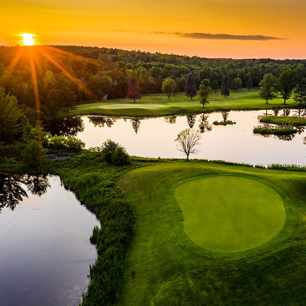 Aerial view of golf course, lakes and sunset